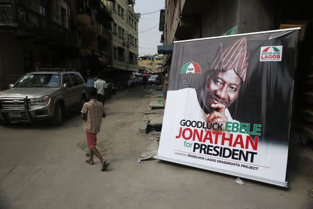 A boy walks near a banner campaigning for Nigeria's President Goodluck Jonathan along a street in Lagos