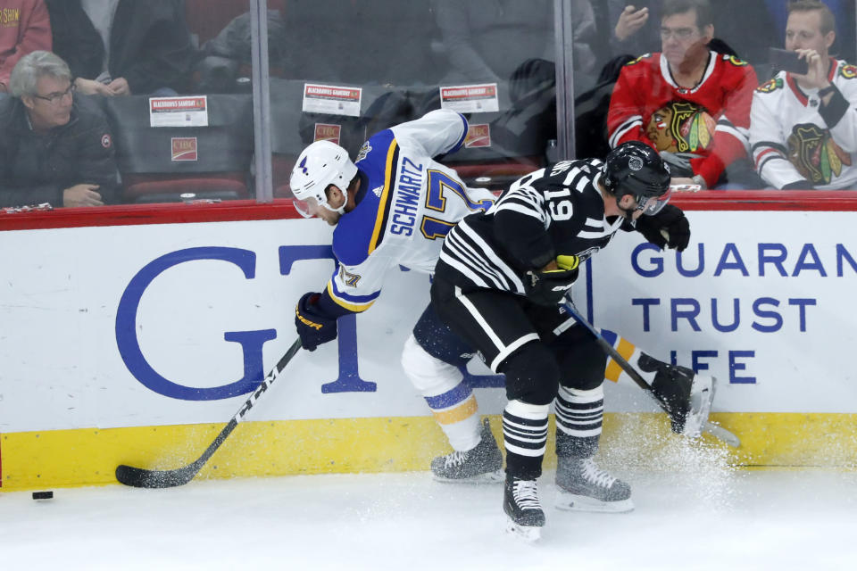 Chicago Blackhawks' Jonathan Toews (19) checks St. Louis Blues' Jaden Schwartz against the boards during the first period of an NHL hockey game Monday, Dec. 2, 2019, in Chicago. (AP Photo/Charles Rex Arbogast)