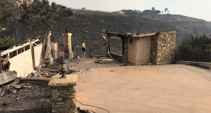 California fires: Tracey Birdsall stands amid the ruins of her Malibu home after it was destroyed by a fire. Source: Supplied