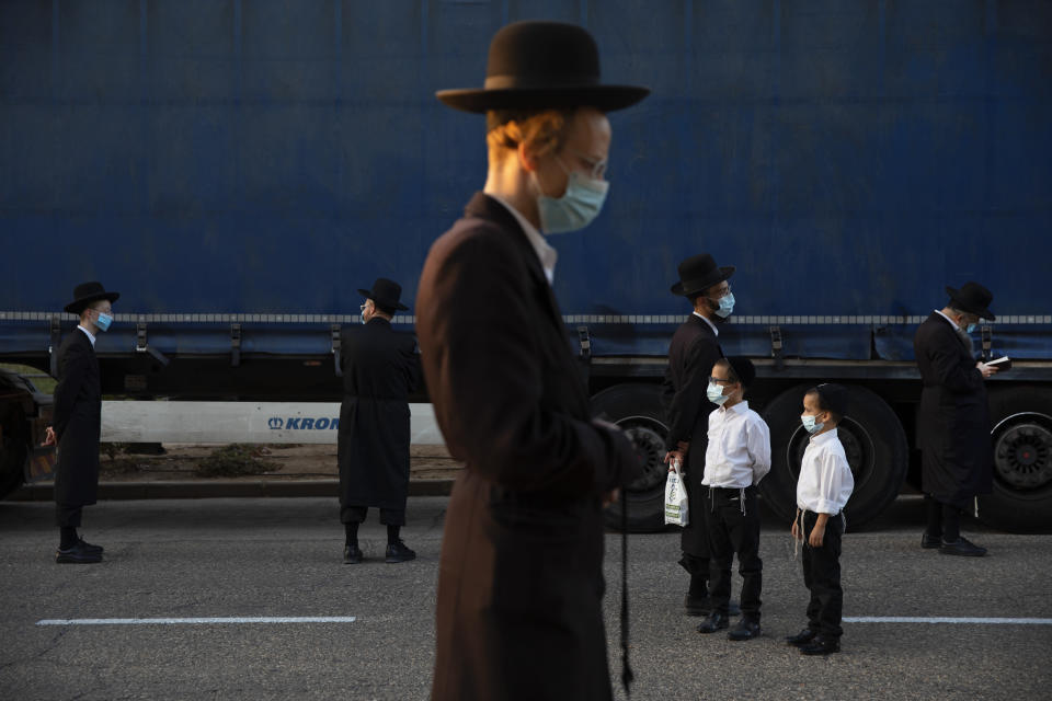 Ultra-Orthodox Jews wear face masks and keep social distancing amid concerns over the country's coronavirus outbreak, during a protest to what they say is incitement against the city and country's religious population, in the southern Israel city of Arad, Monday, Oct 19, 2020. (AP Photo/Oded Balilty)