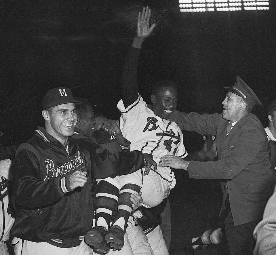 FILE - In this Sept. 23, 1957, file photo, Milwaukee Braves' Hank Aaron is carried from the baseball field by teammates after they won the National League pennant with a 4-2 victory against the St. Louis Cardinals, in Milwaukee. Hank Aaron, who endured racist threats with stoic dignity during his pursuit of Babe Ruth but went on to break the career home run record in the pre-steroids era, died early Friday, Jan. 22, 2021. He was 86. The Atlanta Braves said Aaron died peacefully in his sleep. No cause of death was given. (AP Photo/File)