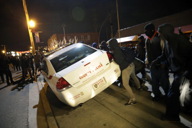 <p>Protesters shove a police car after the announcement of the grand jury decision not to indict police officer Darren Wilson in the fatal shooting of Michael Brown, an unarmed black 18-year-old, Monday, Nov. 24, 2014, in Ferguson, Mo. (AP Photo/David Goldman) </p>