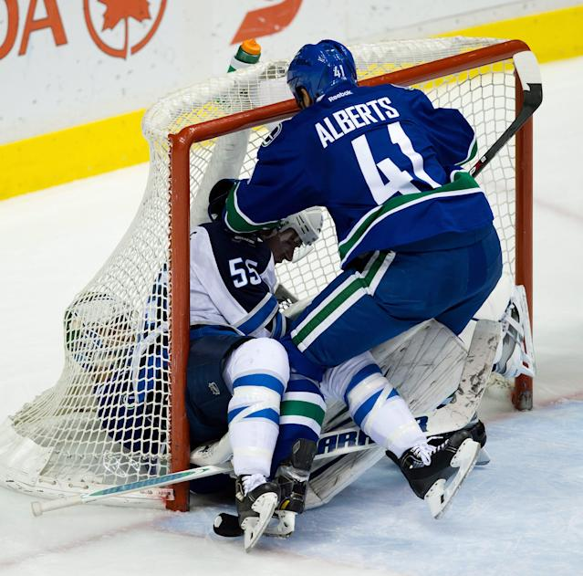 Winnipeg Jets' Mark Scheifele, center, falls on Vancouver Canucks' goalie Eddie Lack, of Sweden, as Andrew Alberts, right, tries to pull him up during the second period of an NHL hockey game in Vancouver, British Columbia, on Sunday, Dec. 22, 2013. (AP Photo/The Canadian Press, Darryl Dyck)