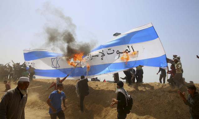 "<p>Palestinian protesters burn a representation of an Israeli flag during clashes with Israeli troops along Gaza's border with Israel, Friday, April 6, 2018. Arabic writing says, "" Death to Israel."" (Photo: Adel Hana/AP) </p>"