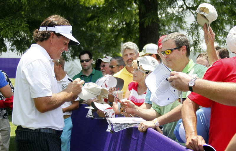 Phil Mickelson signs autographs after completing the first round at the St. Jude Classic golf tournament Thursday, June 6, 2013, in Memphis, Tenn. (AP Photo/Rogelio V. Solis)