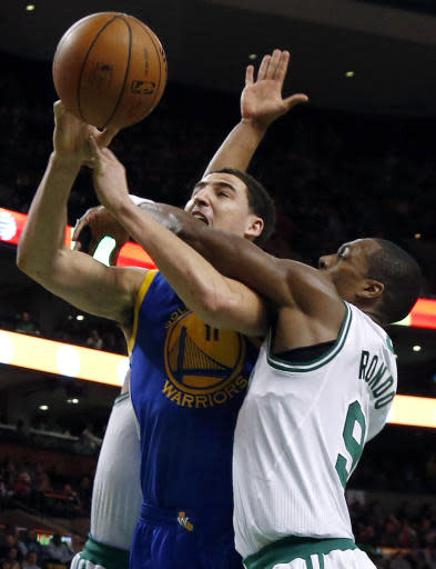 Golden State Warriors guard Klay Thompson (11) is fouled by Boston Celtics guard Rajon Rondo (9) as he goes up for a shot in the second half of an NBA basketball game in Boston, Wednesday, March 5, 2014. The Warriors won 108-88. (AP Photo/Elise Amendola)