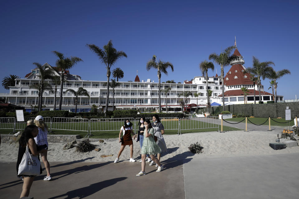 People pass the closed Hotel Del Coronado Thursday, June 11, 2020, in Coronado, Calif. California's tourism industry is gearing back up with the state giving counties the green light to allow hotels, zoos, aquariums, wine tasting rooms and museums to reopen Friday. (AP Photo/Gregory Bull)