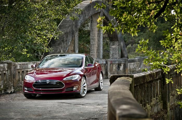 A red 2012 Tesla Model S, a large electric luxury-sports sedan, parked on a stone bridge