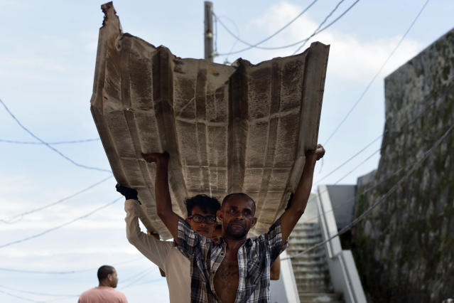 <p>Residents from La Perla carry a piece of metal through the streets after Hurricane Maria, in San Juan, Puerto Rico, Monday, Sept. 25, 2017. The island territory of more than 3 million U.S. citizens is reeling in the devastating wake of Hurricane Maria. (Photo: Carlos Giusti/AP) </p>