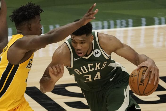 Milwaukee Bucks' Giannis Antetokounmpo tries to drive past Miami Heat's Jimmy Butler during the second half of Game 1 of their NBA basketball first-round playoff series Saturday, May 22, 2021, in Milwaukee. (AP Photo/Morry Gash)