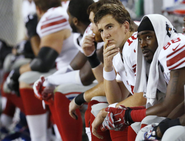 New York Giants quarterback Eli Manning (10) and wide receiver Hakeem Nicks (88) watch from the bench in the first half of an NFL football game against the Chicago Bears, Thursday, Oct. 10, 2013, in Chicago. (AP Photo/Charles Rex Arbogast)