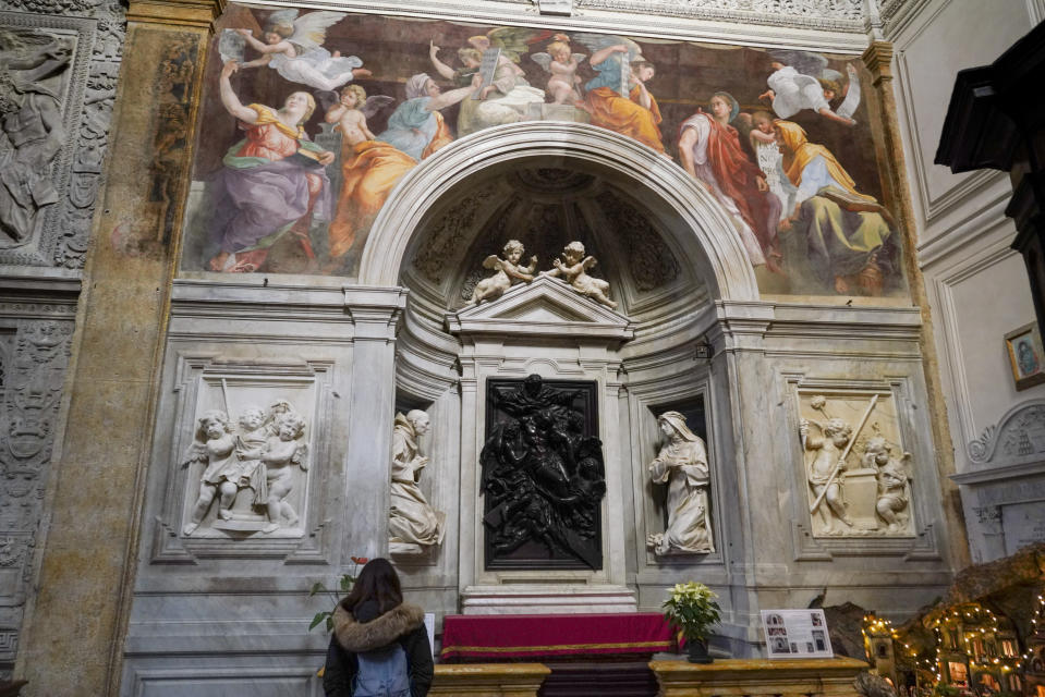 "A woman admires the 1514 fresco ""Sybils receiving instruction from Angels"" by Italian High Renaissance master painter Raffaello Sanzio, known as Raphael, adorns the inside of Santa Maria della Pace church, in Rome, Monday, Dec. 14, 2020. Like elsewhere in Europe, museums and art galleries in Italy were closed this fall to contain the spread of COVID-19, meaning art lovers must rely on virtual tours to catch a glimpse of the treasures held by famous institutions such as the Uffizi in Florence and the Vatican Museums in Rome. However, some exquisite gems of Italy's cultural heritage remain on display in real life inside the country's churches, some of which have collections of renaissance art and iconography that would be the envy of any museum. (AP Photo/Andrew Medichini)"