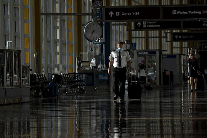 A pilot wearing a protective mask walks through Reagan National Airport in Arlington, Va., on June 9. (Andrew Harrer/Bloomberg via Getty Images)