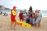 People wearing Christmas-themed attire pose for photos at Bondi Beach in Sydney
