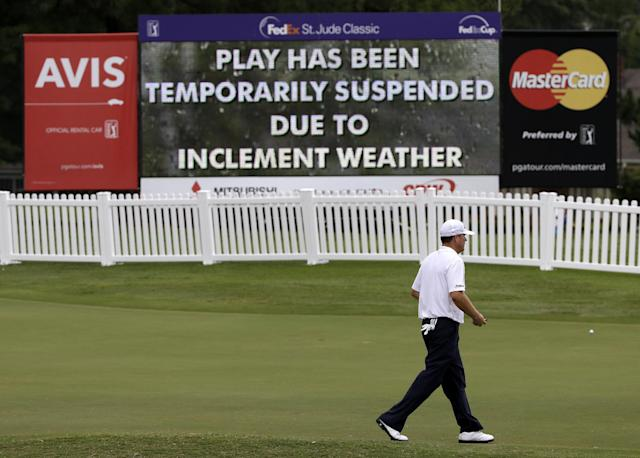 A golfer heads to the clubhouse during a weather delay at the second round of the St. Jude Classic golf tournament Friday, June 6, 2014, in Memphis, Tenn. (AP Photo/Mark Humphrey)
