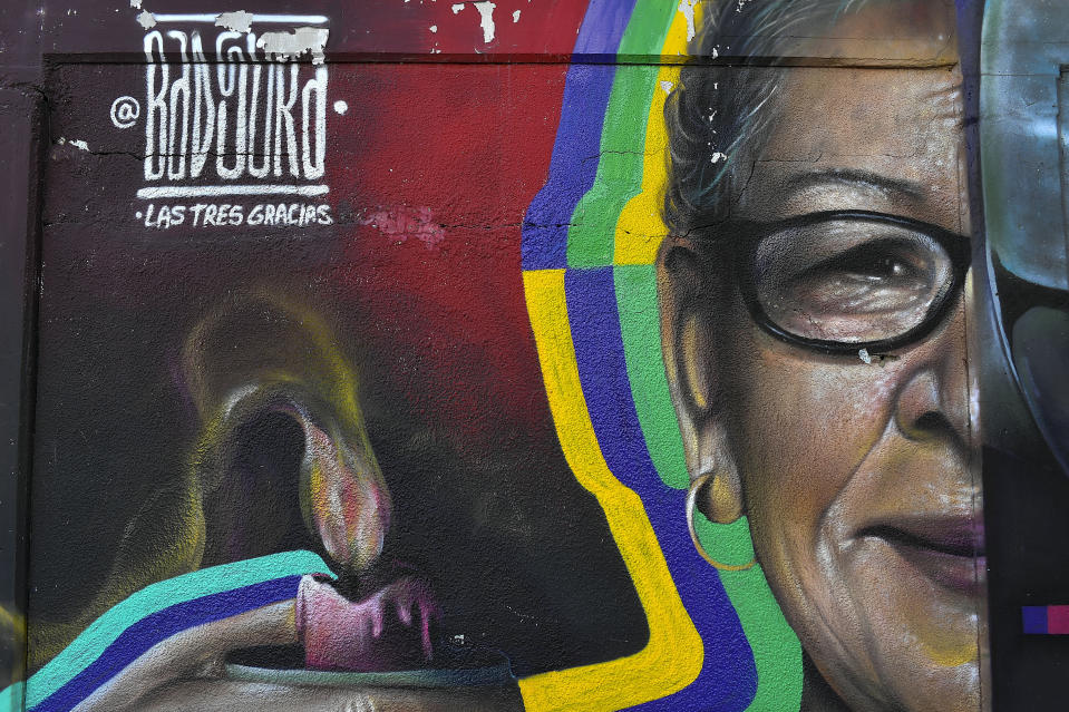 A mural tagged Badsura features a grandmother holding a candle, at Venezuela's Central University in Caracas, Venezuela, Monday, Jan. 11, 2021. Salazar has gained increasing fame for his spray-painted murals of Venezuelans — heroes and everyday folk alike — at a time when the pandemic and economic hardship weigh upon his fellow citizens. (AP Photo/Matias Delacroix)