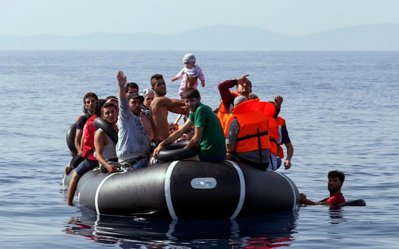 Syrian migrants on board a dinghy travel from the Greek island of Lesbos to the Greek island of Khios - Credit: Selcuk Bulent/AP