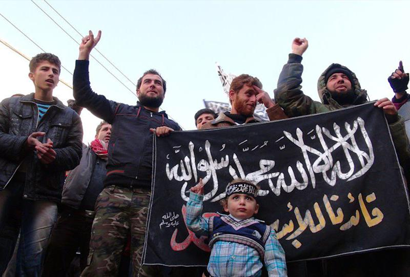 This citizen journalism image taken on Friday, Jan. 25, 2013 and provided by Edlib News Network, ENN, which has been authenticated based on its contents and other AP reporting, shows Syrians chanting slogans and holding an Islamic banner during a demonstration after Friday prayer, at Binnish village in Idlib province, north Syria. (AP Photo/Edlib News Network ENN)