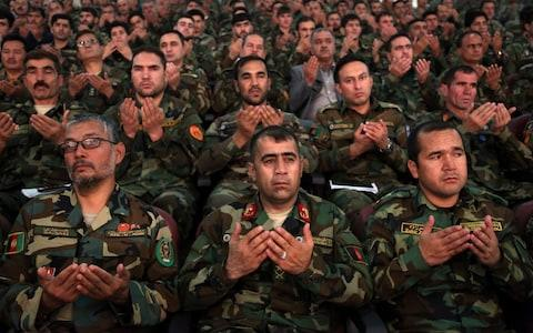Afghan army soldiers pray during a ceremony to introduce the new chief of the intelligence service, in Kabul, Afghanistan, Monday, Sept. 9, 2019. - Credit: AP