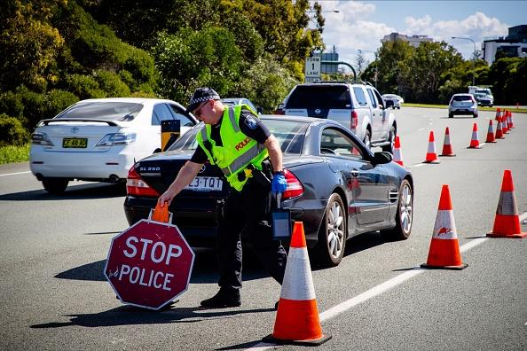 A Queensland police officer moves a stop sign at a vehicle checkpoint on the Pacific Highway on the Queensland - New South Wales border.