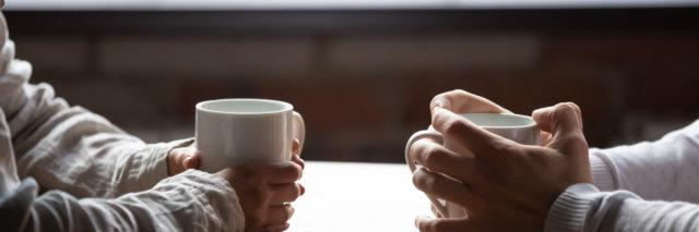 a close up of a woman and a man's hands each holding a coffee cup sitting at a table