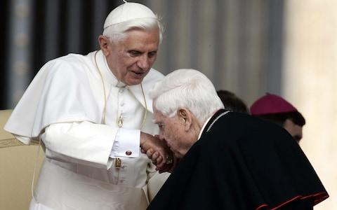 Cardinal Bernard Law, right, kisses Pope Benedict XVI's hand at the end of the weekly general audience in St. Peter's Square at the Vatican, in 2006 - Credit: Plinio Lepri/AP