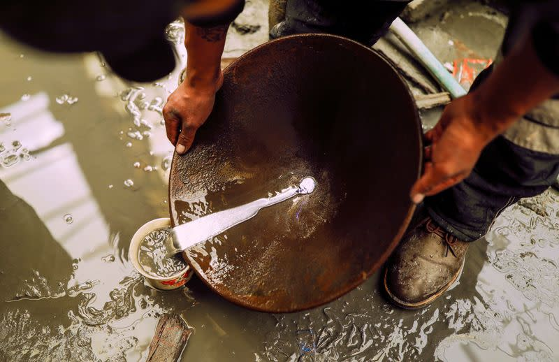 An artisanal gold miner uses a basin and mercury to pan for gold in La Rinconada, in the Andes