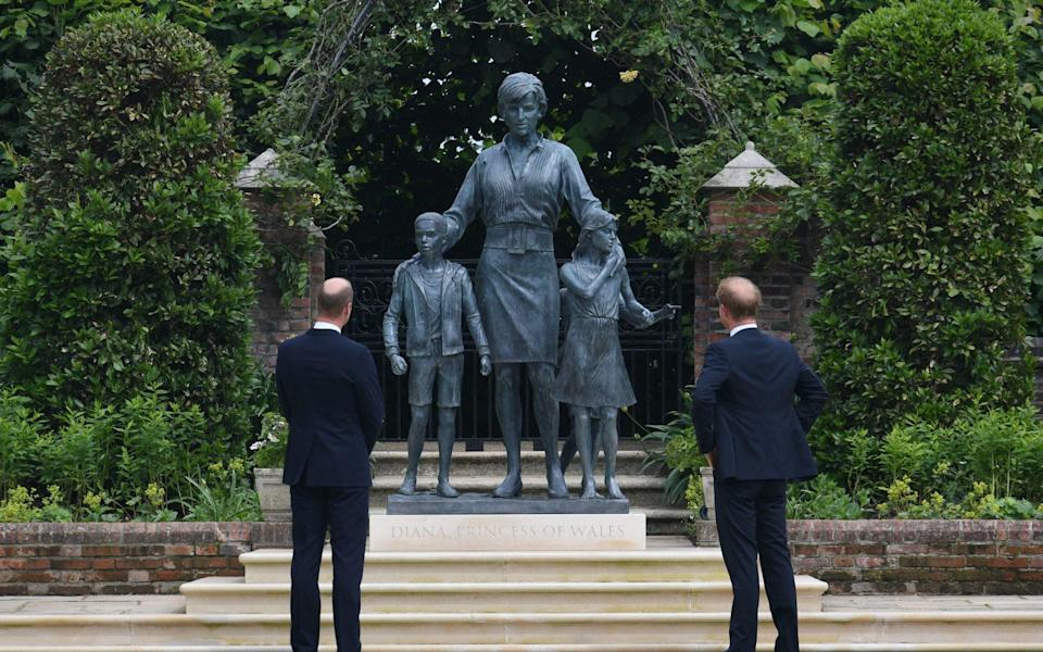 Prince William, Duke of Cambridge (left) and Prince Harry, Duke of Sussex look at a statue they commissioned of their mother Diana, Princess of Wales, in the Sunken Garden at Kensington Palace, on what would have been her 60th birthday on July 1, 2021 in London, - Getty