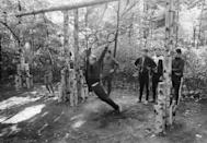 <p>A group of teenagers wait for their turn on an outdoor apparatus. Gymnastic equipment, like the parallel rings and balance bar, became popular in exercise parks. </p>