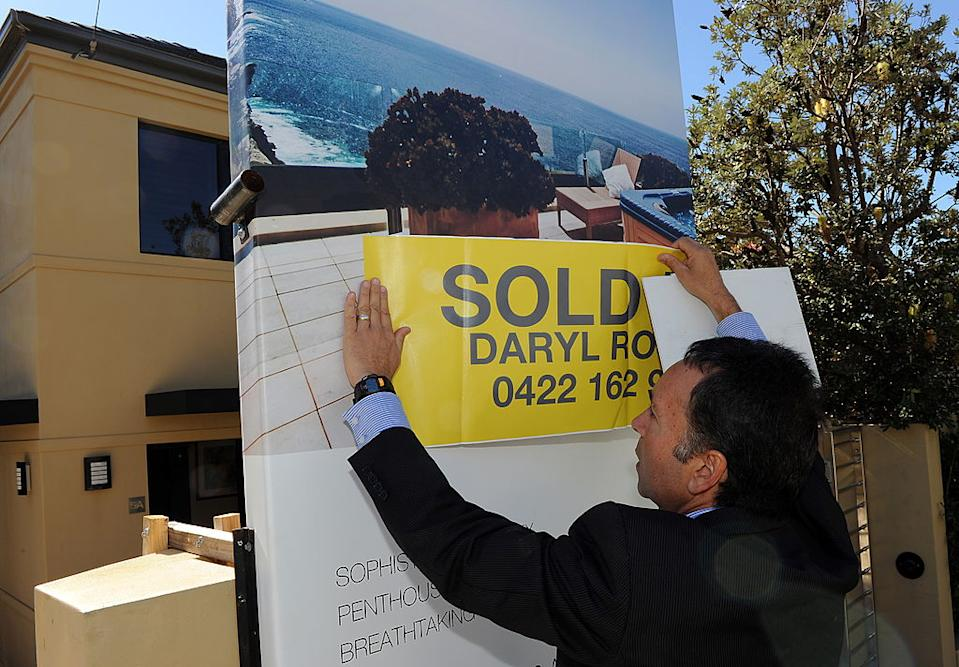 Eastern suburbs real estate agent Daryl Rosen puts a 'sold' sticker over the advertising signage after another successful multi-million dollar house auction in Sydney on May 8, 2010.
