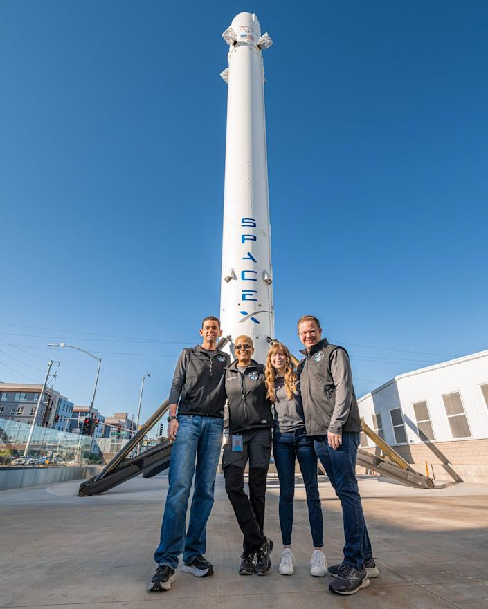 inspiration4 crew pose in front of display falcon 9 rocket