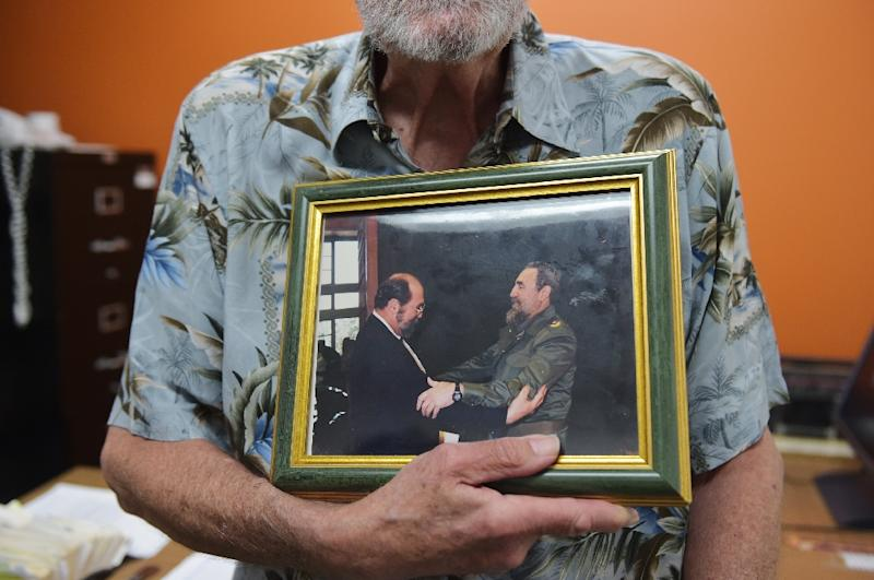 Former US diplomat Wayne Smith poses with a photograph of himself and Fidel Castro in his office at the Center for International Policy on July 2, 2015 in Washington, DC (AFP Photo/Mandel Ngan)