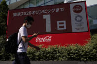 A pedestrian passes by a large electronic display shows one day until the opening ceremony of 2020 Tokyo Olympics, Thursday, July 22, 2021, in Tokyo. (AP Photo/Kiichiro Sato)