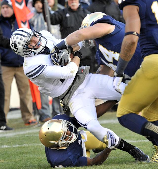 Brigham Young wide receiver Skyley Ridley is tackled by Notre Dame linebacker Carlo Calabrese, right, and cornerback KaiVarae Russell in the first half of an NCAA college football game Saturday, Nov. 23, 2013, in South Bend, Ind. (AP Photo/Joe Raymond)