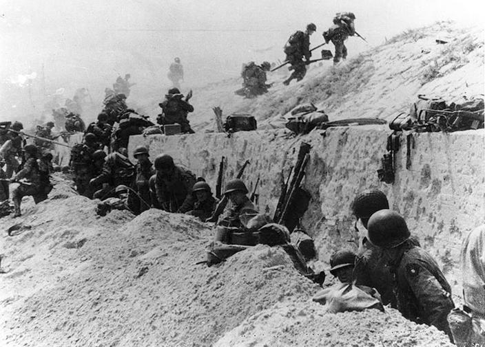 U.S. Army soldiers of the 8th Infantry Regiment, 4th Infantry Division, move out over the seawall on Utah Beach after coming ashore in front of a concrete wall near La Madeleine, France, on June 6, 1944. (Photo: U.S. National Archives/Army Signal Corps Collection/handout via Reuters)