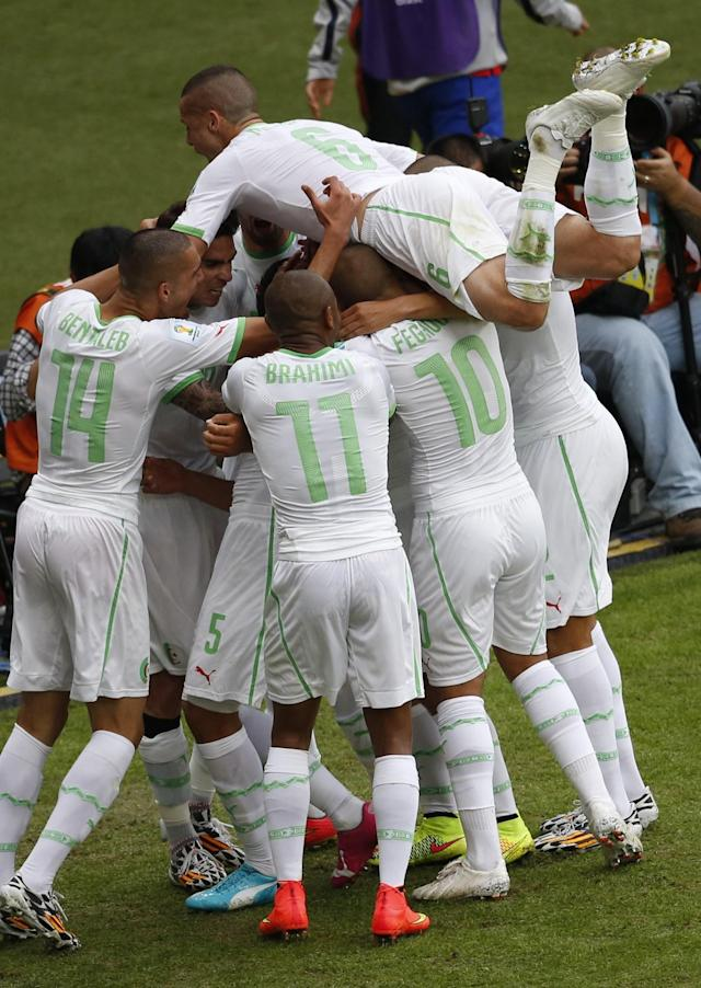 Algeria's Djamel Mesbah (top) celebrates with teammates after the second goal during their 2014 World Cup Group H soccer match against South Korea at the Beira Rio stadium in Porto Alegre June 22, 2014. REUTERS/Marko Djurica (BRAZIL - Tags: SOCCER SPORT WORLD CUP)