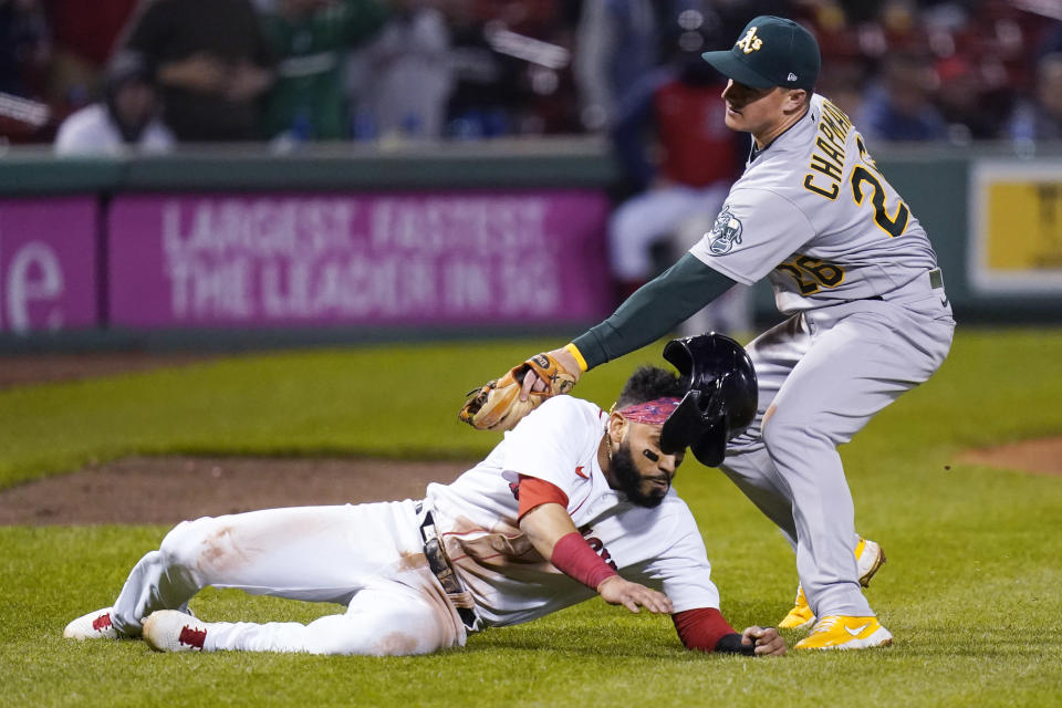 Boston Red Sox's Marwin Gonzalez, left, is tagged out by Oakland Athletics third baseman Matt Chapman after getting caught in a run down during the fifth inning of a baseball game, Wednesday, May 12, 2021, in Boston. (AP Photo/Charles Krupa)