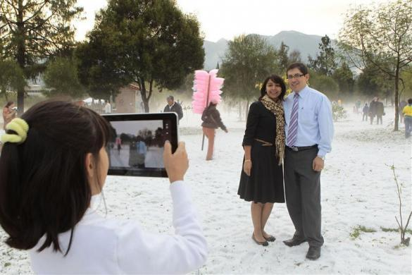 A girl takes pictures of her parents with a tablet computer at the Carolina Park in Quito November 26, 2011 after an unseasonal snowfall.