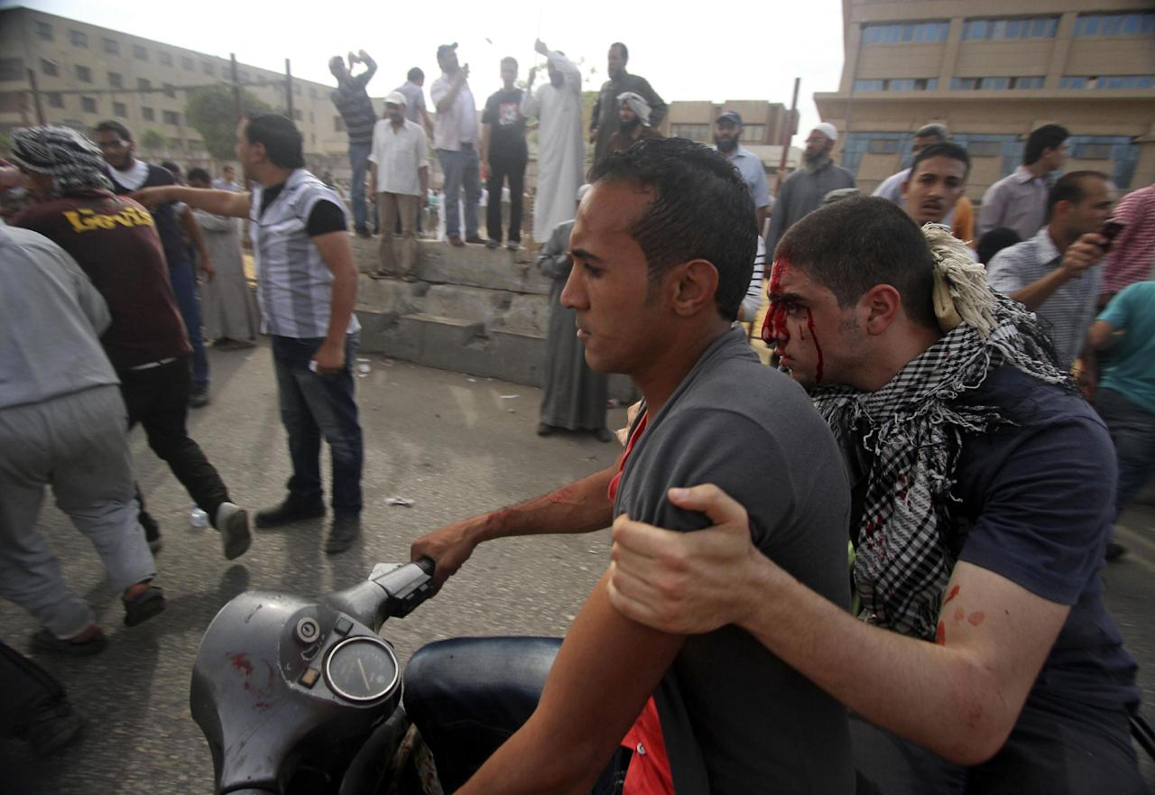 An injured protester is evacuated by motorbike from the site of clashes outside the Ministry of Defense in Cairo, Egypt, Friday, May 4, 2012. Egyptian armed forces and protesters clashed in Cairo on Friday, with troops firing water cannons and tear gas at demonstrators who threw stones as they tried to march on the Defense Ministry, a flashpoint for a new cycle of violence only weeks ahead of presidential elections. (AP Photo/Ahmed Gomaa)