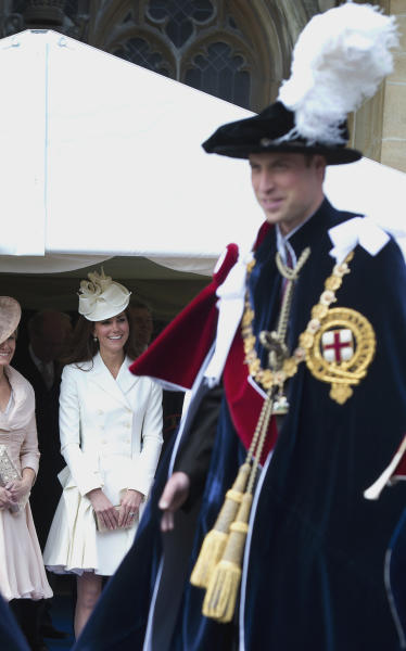 Sophie, Countess of Wessex, right, and Kate, the Duchess of Cambridge, center, watch as Prince William, the Duke of Cambridge, passes by wearing lavish blue velvet robes and black velvet hats with white plumes, during the procession of The Most Noble Order of the Garter in the grounds of Windsor Castle, Windsor, England Monday June 18, 2012. The Most Noble Order of the Garter, founded in 1348, is the highest order of chivalry existing in England. Recipients of the honor are chosen because they have held public office, contributed to national life or served the sovereign personally. The appointment of Knights of the Garter is in the Queen's gift and is made without consulting ministers. (AP Photo/Paul Edwards, Pool)