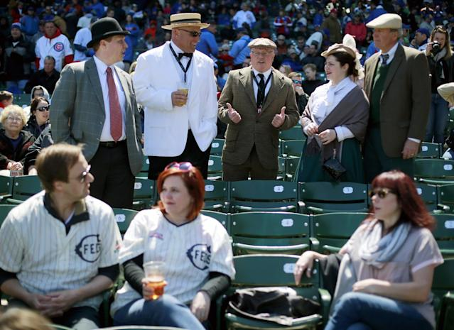 Baseball fans dress in period clothes, top, and the replica 1914 Chicago Federals jersey, bottom left, at the 100th anniversary of the first baseball game at Wrigley Field, before a game between the Arizona Diamondbacks and Chicago Cubs, Wednesday, April 23, 2014, in Chicago. (AP Photo/Charles Rex Arbogast)
