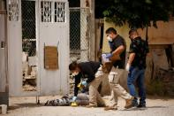 Forensic investigators work at a scene where assailants left a package and a threat message taped to the gate of the house of Leticia Castillo, in Ciudad Juarez