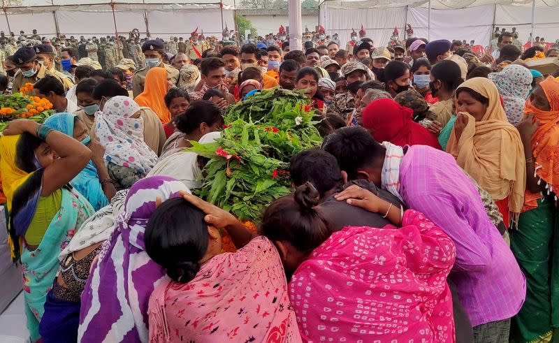 Relatives mourn around a coffin of a security force personnel, who was killed in an attack by Maoist fighters, during a wreath laying ceremony in Bijapur