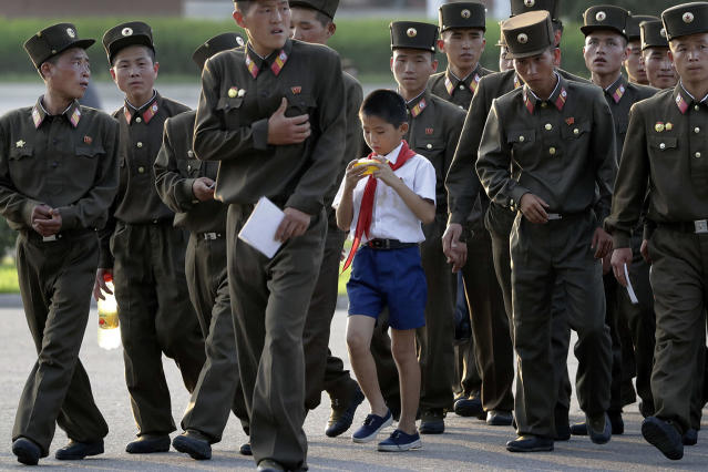 <p>A schoolboy walks among soldiers at the end of a workday July 25, 2017, in Pyongyang, North Korea. (Photo: Wong Maye-E/AP) </p>