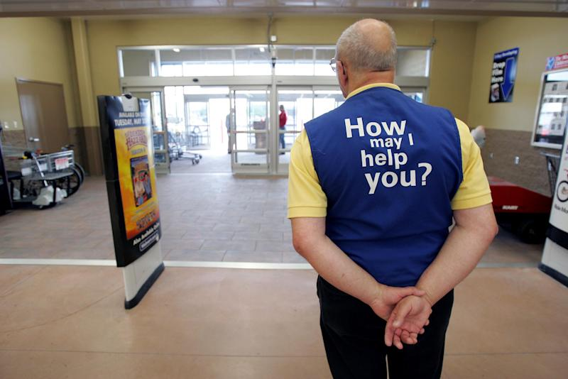 BOWLING GREEN, OH - MAY 17: A Wal-Mart greeter waits to welcome new customers to the new 2,000 square foot Wal-Mart Supercenter store May 17, 2006 in Bowling Green, Ohio. The new store, one of three new supercenters opening today in Ohio, employs 340 people with 60 percent of those working full-time. (Photo by J.D. Pooley/Getty Images)