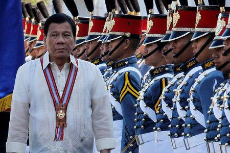 Philippine President Rodrigo Duterte walks past cadets to attend graduation ceremonies at the Philippine Military Academy in Baguio
