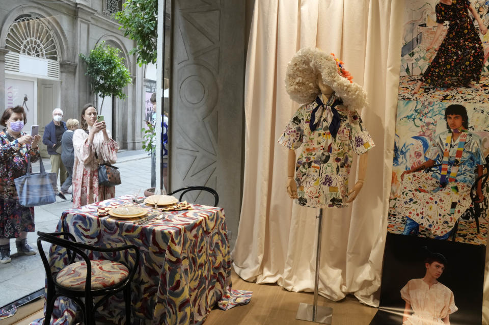 People take pictures of the shop window displaying creations as part of the Arthur Arbesser women's Spring Summer 2022 collection, unveiled during the Fashion Week in Milan, Italy, Saturday, Sept. 25, 2021. (AP Photo/Antonio Calanni)