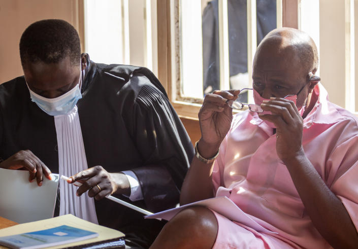 """Paul Rusesabagina, right, whose story inspired the film """"Hotel Rwanda"""", wears a pink prison uniform as he appears for a bail hearing at a court in the capital Kigali, Rwanda Friday, Sept. 25, 2020. Rusesabagina admitted in court that he helped to form the National Liberation Front rebel group in order to assist Rwandan refugees, but denied that he supported any violence or killings. (AP Photo/Muhizi Olivier)"""
