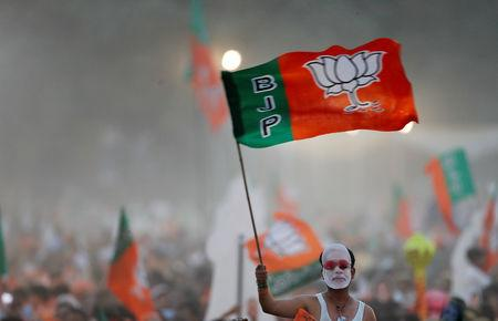 FILE PHOTO: A supporter of India's ruling Bharatiya Janata Party (BJP) waves the party flag during an election campaign rally being addressed by India's Prime Minister Narendra Modi in New Delhi, India, May 8, 2019. REUTERS/Adnan Abidi/File Photo