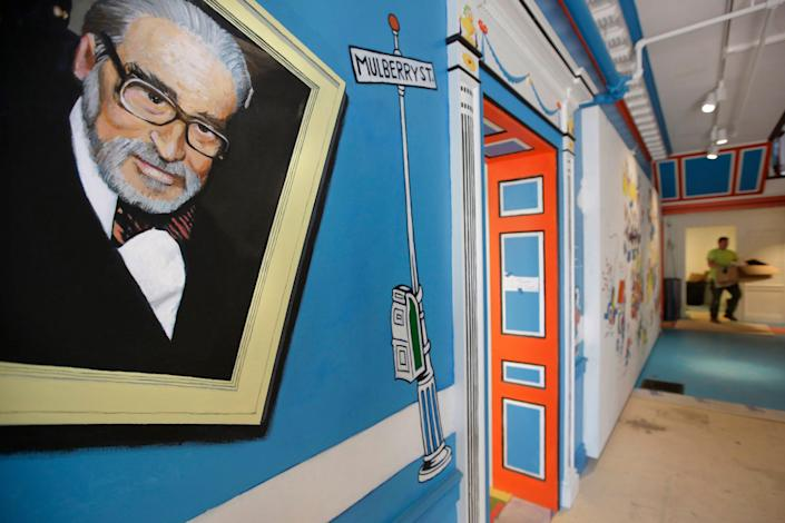 In this May 4, 2017, file photo, a mural that features Theodor Seuss Geisel, left, also known by his pen name Dr. Seuss, covers part of a wall near an entrance at The Amazing World of Dr. Seuss Museum, in Springfield. Dr. Seuss Enterprises, the business that preserves and protects the author and illustrator's legacy, announced Tuesday that it would cease publication of several children's titles because of insensitive and racist imagery.